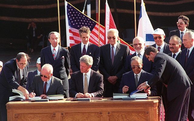 Elyakim Rubinstein, left, holds open the Israel-Jordan peace treaty for Prime Minister Yitzhak Rabin to sign as President Bill Clinton looks on during the 1994 ceremony.