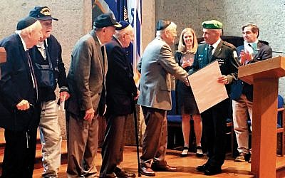 Maj. Gen. Michael Edelstein, in uniform, shakes David Sidorsky's hand as he presents a citation; from left, Harry Bieber, Paul Kaye, Si Spiegelman, and Ralph Lowenstein look on. Donna Kantey Parker and Rafi Marom, members of AVILC's board and co-chairs of the Mickey Marcus Memorial at West Point, applaud in the background. (Photo provided)