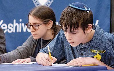 Ezriel Vinar fills in his answers at the USA Bible Quiz at Yeshiva University on May 5, 2019. (David Khabinsky)