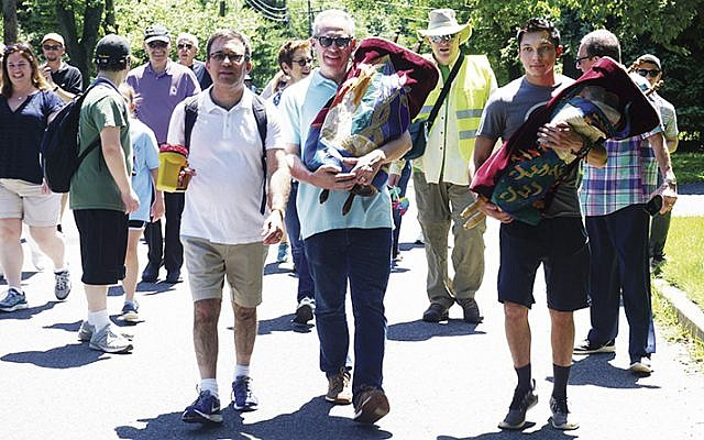 From left, Rabbi David Wizder; Leigh Nacht, carrying a Torah; past Beth El president Marty Kasdan, wearing a yellow vest; and Jarred Cohen, carrying another Torah. They're all from Beth El, on their way to the future at Kol Dorot.