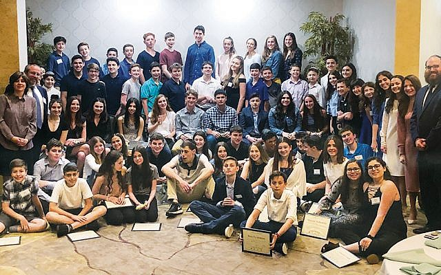 Rabbi Yosef Orenstein, far right, and Estie Orenstein, far left, with teen leadership volunteers. (Photos by Chaya Laine)