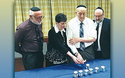 Milton Yudkowitz lights a memorial candle for the victims killed in recent anti-Semitic shootings at the Chabad of Poway and the Tree of Life Synagogue in Pittsburgh. His daughter, Rita Fleischman, is with him. Rabbi Ira Kronenberg, the former director of religious services at Daughters of Miriam, left, and Rabbi Moshe Mirsky, right, the new director, are with them.