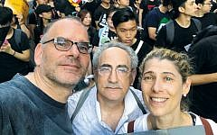 Eli Bitan, David Zweig, and Shani Brownstein, all members of the Jewish community in Hong Kong, stand together as they protest the dissolution of democracy at home.