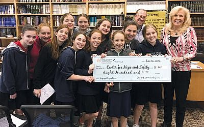 Yeshivat Noam's young philanthropists present a check to Jean Kirch, the director of development at the Center for Hope and Safety.