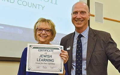 As Roberta Seitzman retired, for the second time, the Jewish Federation & Foundation of Rockland County's CEO, Gary Siepser, presents her with the gift she wanted — a lifetime of Jewish learning. (JF&FRC)