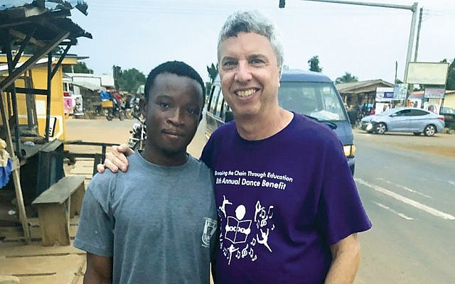 In Ghana, Evan Robbins stands with Michael Mikado, one of the children who had been enslaved and was helped by Breaking the Chain Through Education.