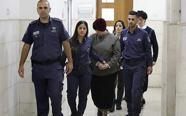 Malka Leifer, center, a former Australian teacher accused of dozens of cases of sexual abuse of girls at a Melbourne school, is escorted by police as she arrives for a hearing at the District Court in Jerusalem, Feb. 27, 2018. (Ahmad Gharabli/AFP/Getty Images)