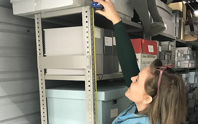 The museum's project coordinator, Anna Tucker, measures shelves used to store artifacts ahead of the move last month. (Courtesy of the Museum of the Southern Jewish Experience)