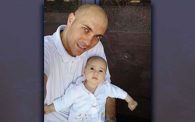 Oded Grinstein cradles his infant daughter, who suffered from a rare and aggressive cancer.