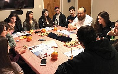 Rabbi Yosef Orenstein, the head of Valley Chabad's Teen Leadership Initiative, sits with students as they debate issues. (Valley Chabad)