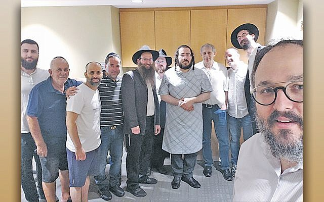 Chaim Blumenfeld, in his hospital gown, stands next to poet Yehoshua November, on his left, wearing a black hat. Rabbi Mendy Kaminker of Chabad of Hackensack stands at the far right, craning into the photo, and Rabbi Chanoch Kaplan of the Chabad Jewish Center of NWBC in Franklin Lakes, front right, takes the selfie. They are among the men who showed up for the midnight minyan. (Courtesy Chabad of Hackensack)