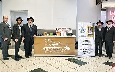 Newark Liberty Airport manager Frank Radics, left, Rabbis Avremy and Mordechai Kanelsky, Rabbi Dovid Wilansky, and Dovid Hoffer at the Bris Avrohom Jewish information stand. (Courtesy Bris Avrohom)