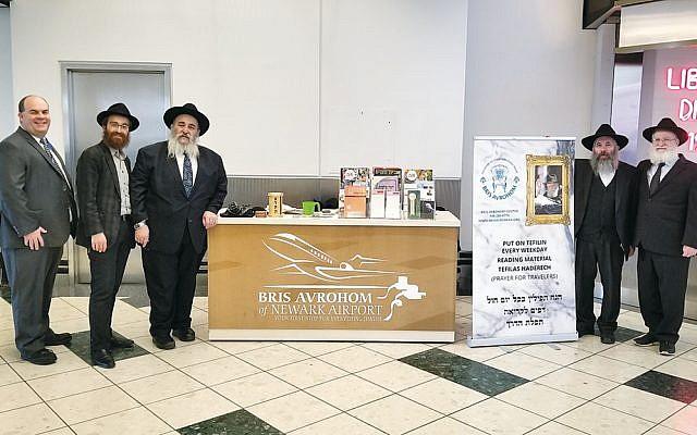 Newark Liberty Airport manager Frank Radics, left, Rabbis Avremy and Mordechai Kanelsky, Rabbi Dovid Wilansky, and Dovid Hoffer at the Bris Avrohom Jewish information stand. (Courtesy Bris Avrohom)
