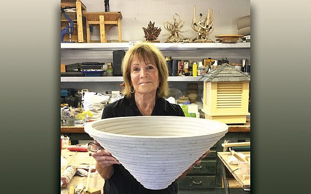 Ronnie Streichler, standing in her workshop, holds a bowl she made from drywall and caulking.