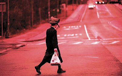 A young chasidic man crosses a street in Monsey on April 5, 2019. (Johannes Eisele/AFP/Getty Images)