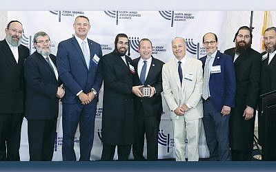 The NJJBA board of directors presents the Excellence of Leadership award to Congressman Josh Gottheimer, fifth from left, at the group's luncheon in Newark. (Lenchevsky Images)