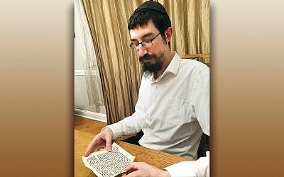 Rabbi Mendy Kaminker of Chabad of Hackensack checks a mezuzah scroll. (Photo provided)