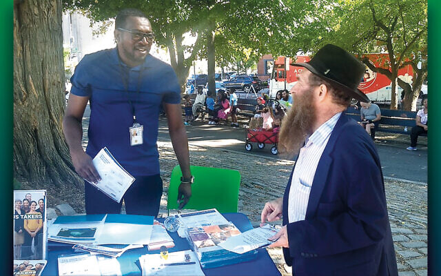 Rabbi Eli Cohen, right, the executive director of the Crown Heights Community Center, talks with a census volunteer at the #OneCrownHeights festival in Brooklyn on September 15, 2019. (Ben Sales)
