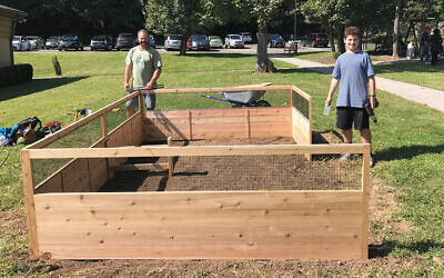 Ian Roth and his father, Brad, work on building the raised garden bed for Ian's bar mitzvah project.