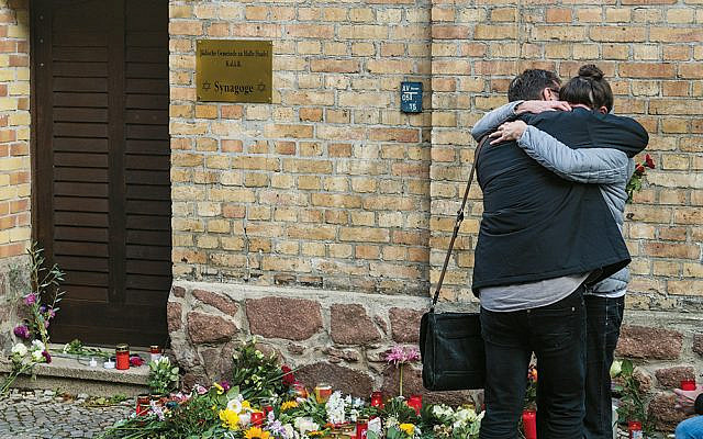 People mourn in front of the entrance to the synagogue on October 10, 2019, in Halle, Germany. (Jens Schlueter/Getty Images)