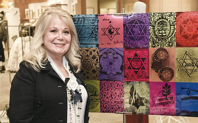 """Jackie Koby stands by Marc Bennett's """"The History of the Star of David Art."""" (Joe Epstein courtesy of Gale Branding)"""