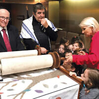 At Temple Beth Sholom in Fair Lawn, Debbie Propper Lesnoy, the director of the shul's Helen Troum Nursery School, shows the Torah to the children as Alan Lewis and Rabbi Baruch Zeilicovich re-rolled the scroll to begin the new year. (Courtesy Temple Beth Sholom)