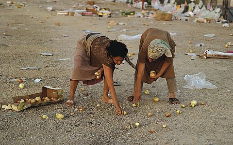 """Ruth and Naomi glean onions after an open-air market; they remind viewers of Jean-François Millet's """"The Gleaners."""" """"The hardened women gather onions created from their tears which turn to gold in their hands,"""" Adi Nes says."""