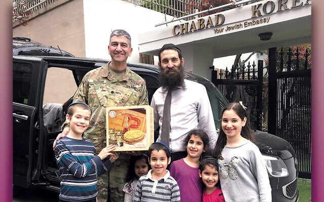 Rabbi Osher Litzman with some of his children and U.S. Army Chaplain Rabbi Henri Soussan in Seoul as they receive Passover supplies.