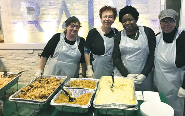 Volunteers at the Teaneck Helping Hands Food Pantry are ready to serve Thanksgiving fare.