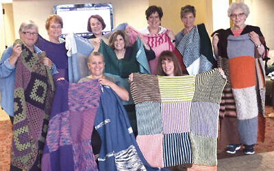 The knitters include, back row, Sandy Silberman Barbara Grossman, Suzy Kaplan, Eva Jakob, Judi Neidenberg, Beth Edwards, and Sally Lax. Susan Liebeskind and Barbara Selman are in the front.