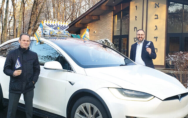 Gary Rozenbaum, left, and Rabbi Chanoch Kaplan stand with one of Moonlight Limo's cars decked out for the Car-Menorah Parade. (Courtesy Chabad)