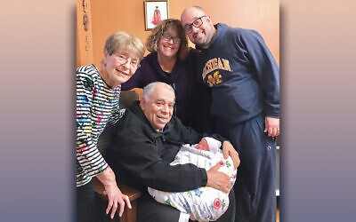 New great-grandfather Allan Eisenkraft holds the baby as, from left, great-grandmother Estelle Eisenkraft, grandmother Sharon Rappaport, and new father Brian Rappaport beam.