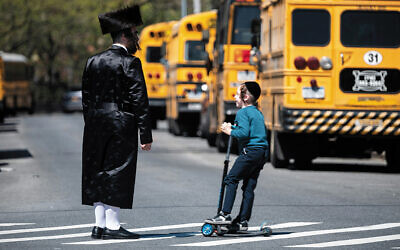 A chasidic man and boy stand on a street in Williamsburg on April 24, 2019. (Johannes Eisele/AFP via Getty Images)