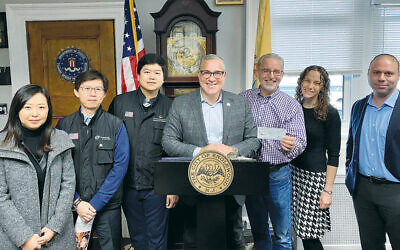 Leah Huang, executive secretary of Seoul Trading Asian Grocery; Jay Lee, manager of the firm; and Tae Ho Kwon, CEO of Seoul Trading, with Mayor Wildes, Evan Sohn, former Kesher Synagogue president, and shul leaders.