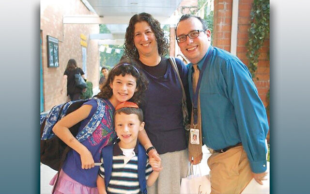 On the first day of school in 2015, Rabbi Fred Elias and his wife, Michelle, stand with their children, Kayla and Eitan.