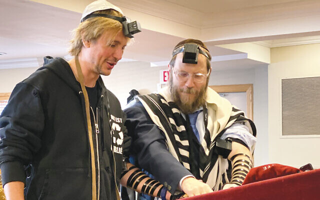 Jonathan Cheban, left, putting on tefillin with the help of Rabbi Levi Konikov of Chabad of Fort Lee. (Courtesy Chabad)