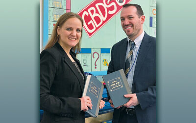 Rabbi Jennifer Schlosberg and Rabbi Micah Liben with donated siddurim. (Photo courtesy GRJC)