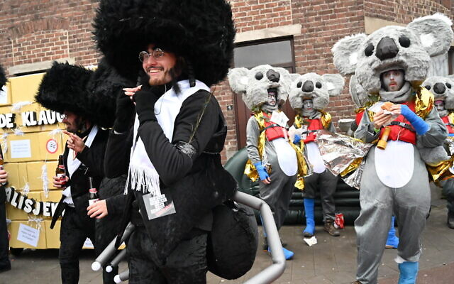 Participants in the Aalst Carnival in Belgium wear costumes combining the clothes of haredi Orthodox Jews with ant parts, Feb. 23, 2020. (Cnaan Liphshiz)