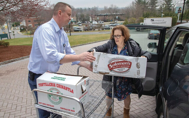 Debbie Ross hands off dinner from Sender's Smoke Joint in Teaneck to David Van Bever, the director of Environmental Services, for his hardworking staff. (Photos by Areyvut)