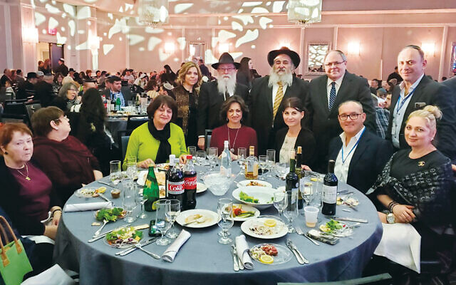 In the back row, from left, are Kreina and Rabbi Baruch Lepkivker, Bris Avrohom's program director; Rabbi Mordechai Kanelsky, BA's executive director, and his wife, Shterney, seated in the middle (in maroon); Ambassador Dani Dayan, and guests. (Courtesy Bris Avrohom)
