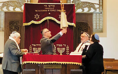On President's Day, Englewood Mayor Michael Wildes lifts the Torah for Hagbah, as Rabbi Joseph Prouser of Temple Emanuel of North Jersey looks on. (TENJ)