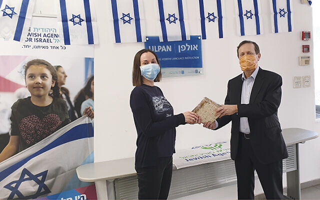 Isaac Herzog, the chair of the Jewish Agency, at right, delivered matzahs to young new immigrants who were about to observe their first Passover in Israel. (The Jewish Agency for Israel)