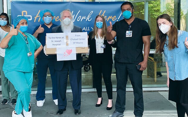 Rabbi Michel Gurkov, above center, stands with hospital staff at Saint Joseph Regional Medical Center in Wayne. His daughter, Rosie, is at right. (Courtesy Wayne Chabad)