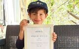 Six-year-old Imri Elya displays the ancient tablet and the certificate of recognition given to him by the Israel Antiquities Authority to thank him for turning it in. (Courtesy of Israel Antiquities Authority)