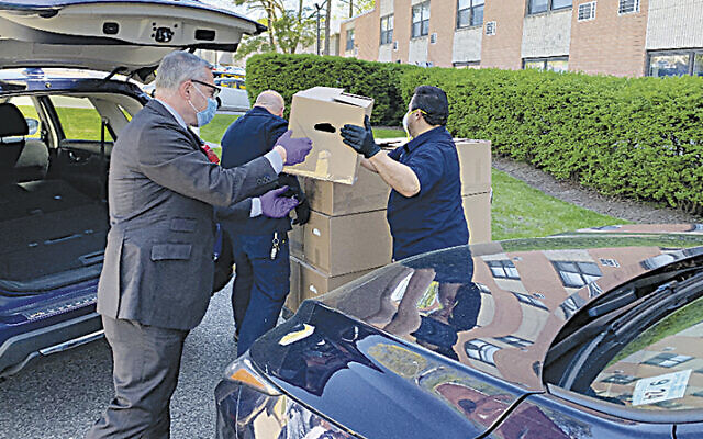 Englewood Mayor Michael Wildes helps unload a delivery of 50 meals. (courtesy Moriah)
