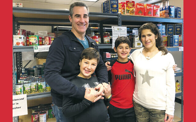 Gregory Michaels, with his father, Adam, brother, Alex, and mother, Natalya, volunteering pre-pandemic at the JFCS food pantry. (Photos courtesy JFCS)