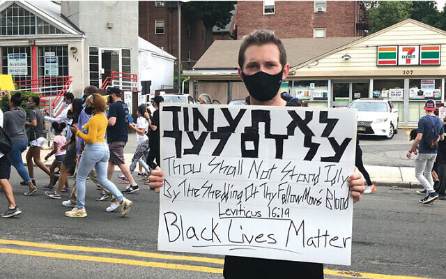 A masked protester holds a sign quoting the Bible in Hebrew and in English. (JAMES L. JANOFF)