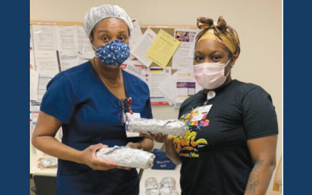 Two workers at Montefiore Nyack Hospital receiving meals from the shul. (Courtesy RTR)