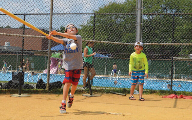 Last year, pre-covid, campers play tennis at the Neil Klatskin Day Camp at the Kaplen JCC on the Palisades in Tenafly; behind them, the JCC's pool is busy. (JCCOTP)