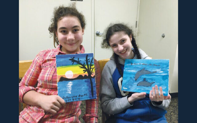 Two Sinai students hold up the art they've created.